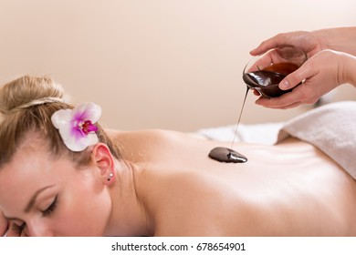Woman lying in a beauty parlour, enjoying relaxing back massage with chocolate. Focus on the chocolate being poured out of bowl