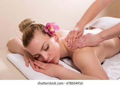 Woman lying in a beauty parlour, enjoying relaxing back massage