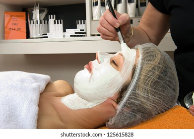 A woman is lying in a beauty salon and getting a facial mask on her face with a brush