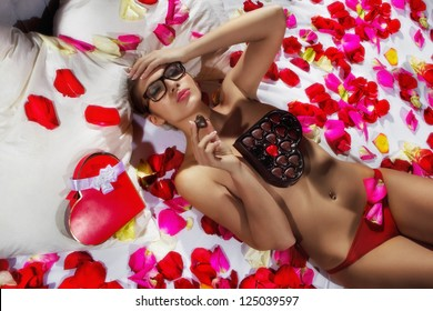 Woman lying in bed covered by Flower Petals with chocolate candy shaped like a heart