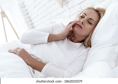 Woman lying in bed and holding on to a bad tooth. Woman with chronic tooth disease lies in bed. Woman in white bed with severe pain in her teeth.