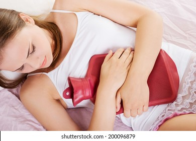 Woman lying in bed with hot water bag and holding it on her belly.