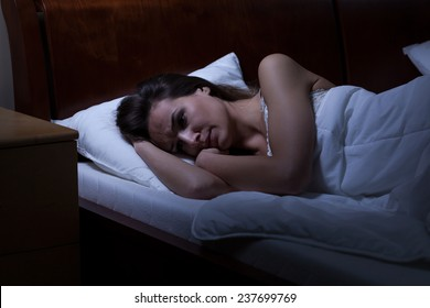 Woman lying in bed with opened eyes