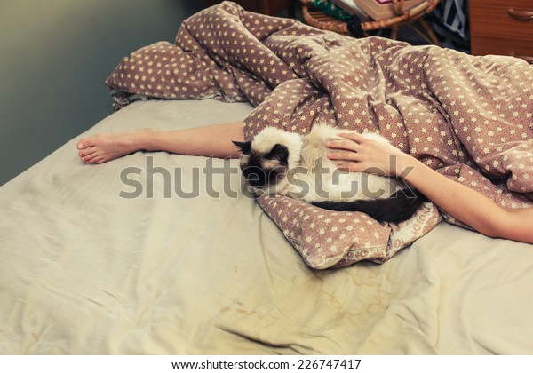 A woman is lying in bed and is petting a cat