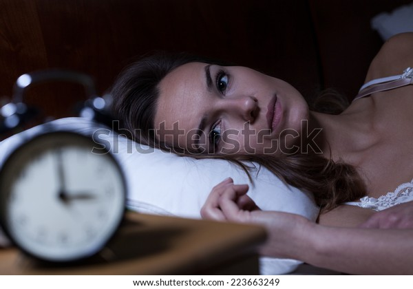 Woman lying in bed suffering from insomnia