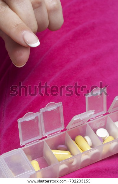 Woman lying in bed taking pills from a special container. Holds a container and a pill.