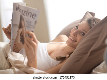 Woman lying in bed while reading a magazine