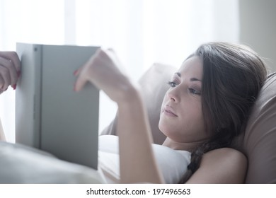 Woman lying in bed while reading a book