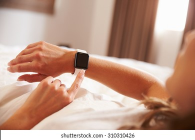 Woman Lying In Bed Whilst Using Smart Watch