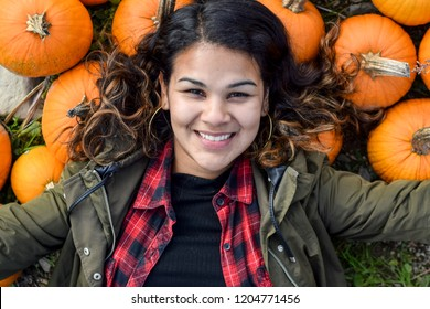Woman lying in a bushel of pumpkings.  Smiling woman in autumn with pumpkins.
