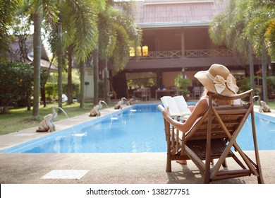 Woman lying in a deck-chair in a hotel and enjoying a book reading