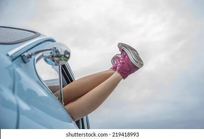 woman lying down in her car. legs out. concept of freedom and carefree. Car and shoes give a vintage touch to the image