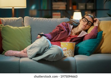 Woman lying down on the sofa at home and watching TV