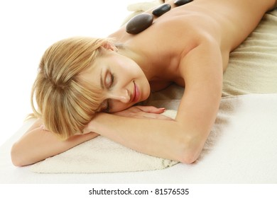 A woman lying during a spa stone treatment over white