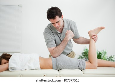Woman lying forward while a man stretched her leg in a room