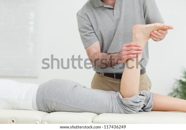 Frau, die vorn liegt, während eine Physiotherapeutin ihr Bein im Raum untersucht
