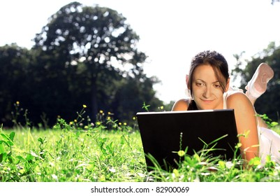 Woman lying in grass with laptop