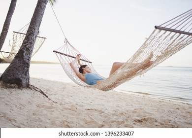 A woman is lying in a hammock among the trees on an island near the sea