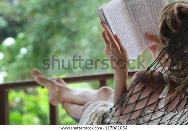 Woman lying in a hammock in a garden and enjoying a book reading