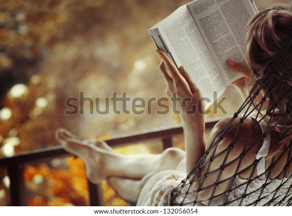Frau in einer Hängematte im Garten und in einem Buch lesen