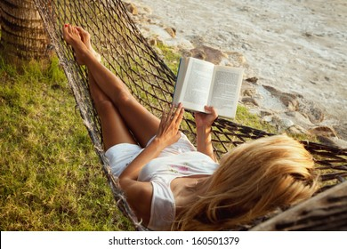 Woman lying in a hammock on the beach and enjoying a book reading