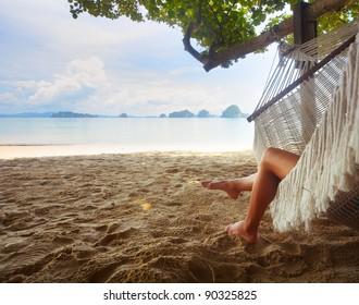 Woman lying in a hammock in tree's shadow on a beach