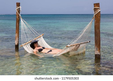Woman lying in a hammock which is partially submerged in the sea.