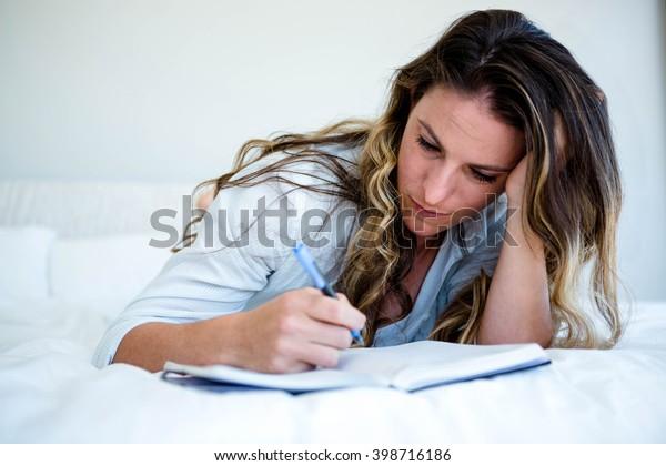 ベッドに横になって悲しげに見え、本に書いている人