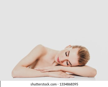 Woman lying her head on arms with closed eyes, on white background.