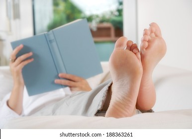 Woman lying with legs raised on a couch and reading a book.