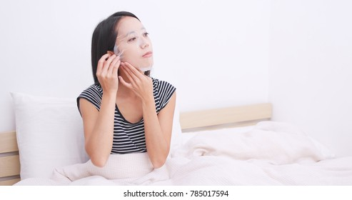 Woman lying on bed and apply paper mask on face