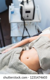 Woman lying on bed at beauty clinic, having a injection lipolysis treatment.