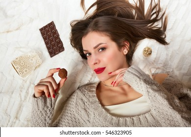 Woman lying on the bed eating a chocolate