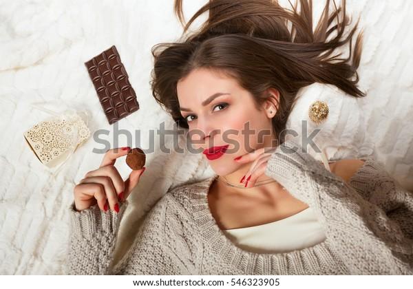 ベッドに横になってチョコレートを食べている女性