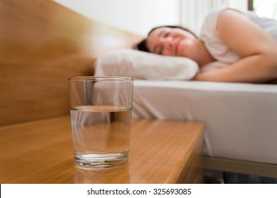 woman lying on bed with glass of mineral water on the nightstand