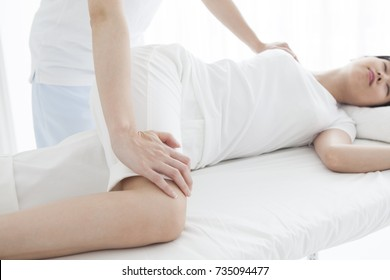 A woman lying on the bed and receiving rehabilitation.