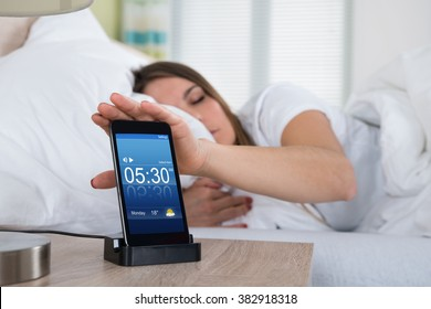 Woman Lying On Bed Snoozing Alarm On Mobile Phone Screen