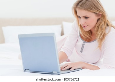 A woman lying on the bed, using a laptop and looking at the screen.
