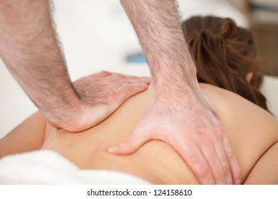 Woman lying on the belly while being massaging with two hands of doctor indoors