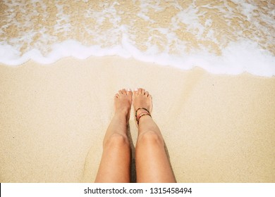 woman lying on the caribbean yellow sand near the transparent water. concept of vacation and travel in relaxation - nudism and naked legs enjoying the sun bath and gone tanned