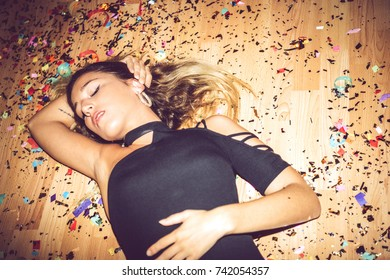 Woman lying on dirty floor covered with confetti in provocative pose during private party.