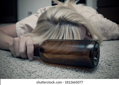 Woman lying on the floor with an empty alcohol bottle ans sleeping, overdosage and female alcoholism concept.