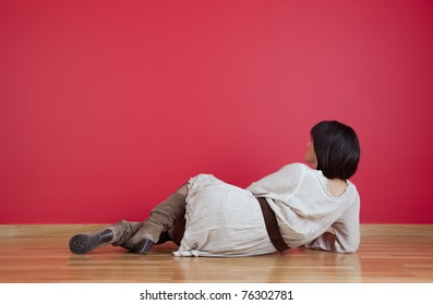 Woman lying on the floor looking to her fresh new red wall