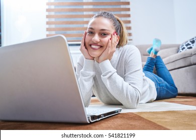 woman lying on floor and using laptop
