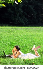 Woman lying on grass with a laptop