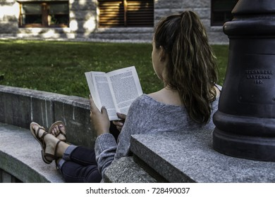 Woman lying on the grass in reading a book with a pink highlighter