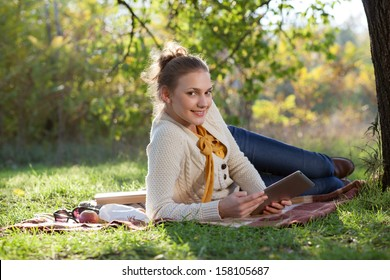 woman lying on green grass with tablet