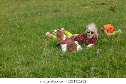 Woman lying on green meadow resting with her pet - Cavalier King Charles Spaniel - who is barking