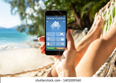 Woman Lying On Hammock Using Smart Home Control On Mobile Phone At Beach
