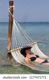 Woman lying on a hammock which is partly submerged in the sea.